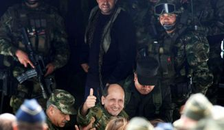 Colombian Army Gen. Luis Mendieta gives a thumb up as he arrives Monday at a military base in Bogota. He and three other FARC hostages were rescued Sunday after 12 years in the jungle. (Associated Press)