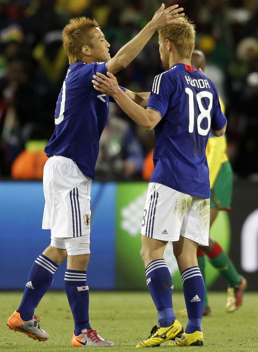 Japan's Keisuke Honda, right, and Japan's Junichi Inamoto, left, celebrate their victory following the World Cup group E soccer match between Japan and Cameroon at Free State Stadium in Bloemfontein, South Africa, Monday, June 14, 2010. Japan won 1-0. (AP Photo/Shuji Kajiyama)