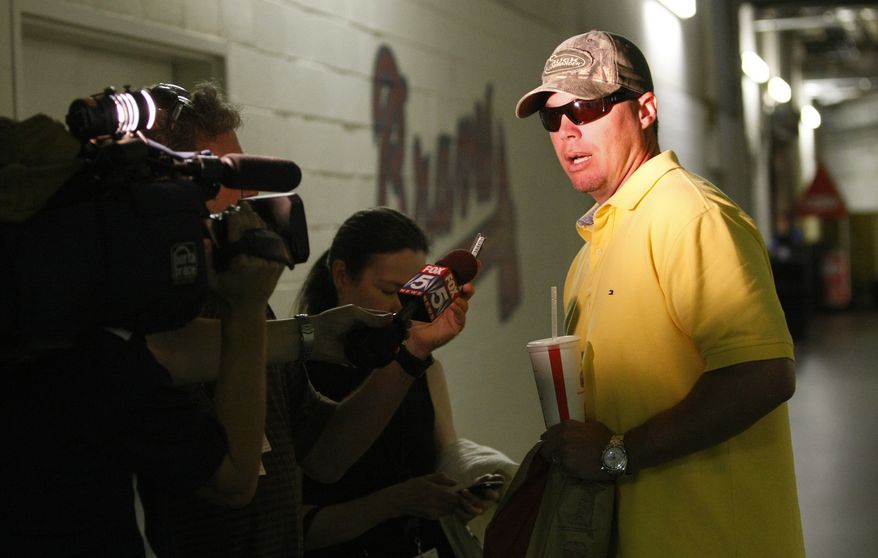 Atlanta Braves baseball player Chipper Jones, right, speaks with the media as he arrives outside the Braves clubhouse at Turner Field in Atlanta on Tuesday, June 15, 2010. Struggling through another disappointing season, Jones told The Associated Press he would meet with team officials Tuesday to discuss his future and acknowledged that he's considering retirement. (AP Photo/The Atlanta Journal & Constitution, Curtis Compton)