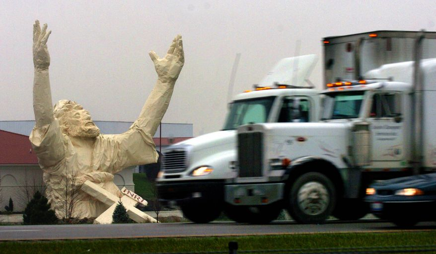 A Nov. 17, 2004 file photo shows traffic on I-75 just north of the Monroe, Ohio, going by a six-story-high statue of Jesus under construction at the Solid Rock Church Nov. 17, 2004. The 62-foot-tall statue made of plastic foam and fiberglass over a steel frame was stuck by lightning and destroyed Monday, June 14, 2010. (AP Photo/The Enquirer, Glenn Hartong/file)