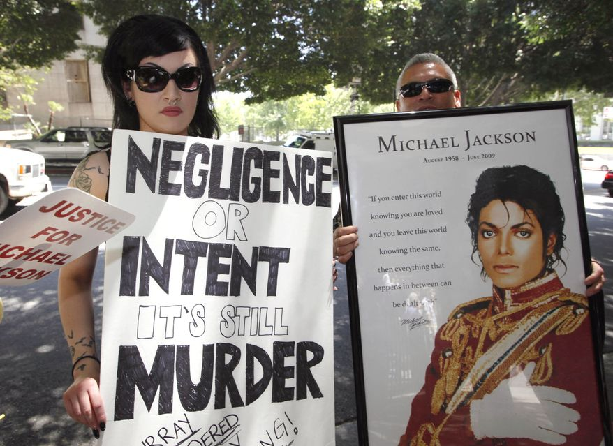 Sheila Baragas, left, and her father, Sam, hold posters in support of Michael Jackson and posters critical of Dr. Conrad Murray outside a Los Angeles courthouse Monday, June 14, 2010. (AP photo)