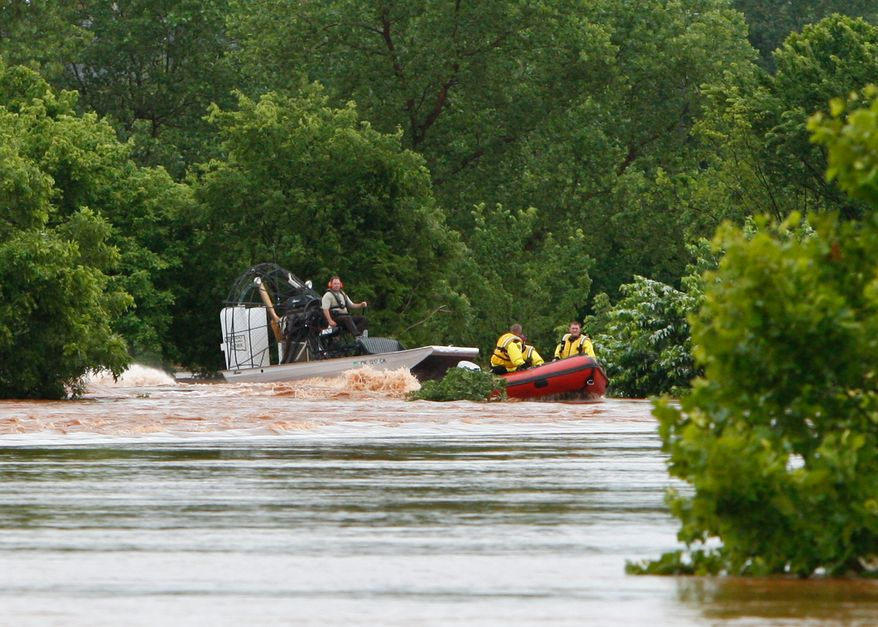 Oklahoma Highway Patrol officers and Oklahoma City firefighters search for people stranded by flood waters in Oklahoma City after heavy rain hit the area on Monday, June 14, 2010. (AP Photo/Alonzo Adams)