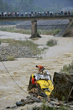 Chinese rescuers work to pull up a bus devoured by the flash floods in Nanping, in eastern China's Fujian province, on Tuesday, June 15, 2010. At least 24 people are missing after flash floods and landslides triggered by heavy rains engulfed two vehicles, according to state media. (AP Photo)