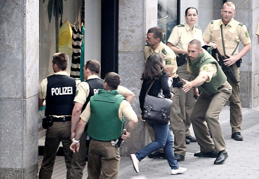 Police officers outside an H&M fashion store in central Leipzig, Germany, secure pedestrians on Tuesday, June 15, 2010, as an armed man inside holds several hostages, who were released without injury several hours later. Police spokeswoman Uta Barthel told the Associated Press that a 41-year-old man was in custody and that authorities believe psychological problems led to the hostage-taking. She declined to say how many hostages were taken, but said all were being cared for by medical professionals. (AP Photo/ddp/Sebastian Willnow)