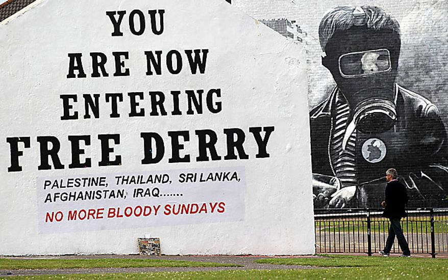 A man walks past a Bloody Sunday mural in the Bogside area of Londonderry, Northern Ireland, on Tuesday, June 15, 2010. Relatives and family members of the dead made their way to the Guildhall to receive a preview of the Saville Report, which details the British government's findings from the investigation into Bloody Sunday, the 1972 killing of 13 Catholic demonstrators by British troops. The probe began in 1998 and became the most expensive in British legal history as it gathered evidence from 2,500 witnesses, including troops who opened fire that day. (AP Photo/Peter Morrison)