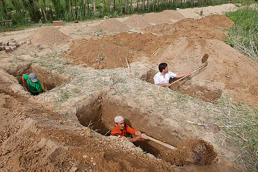 Uzbek men dig graves in the southern Kyrgyz city of Osh on Tuesday, June 15, 2010, in preparation for burying victims who died during ethnic rioting between Kyrgyz and ethnic Uzbeks. The rioting has killed at least several hundred people, or roughly double official figures, the Red Cross said Tuesday as new reports strengthened suspicions that the rioting in Kyrgyzstan was started deliberately.  (AP Photo/Sergei Grits)