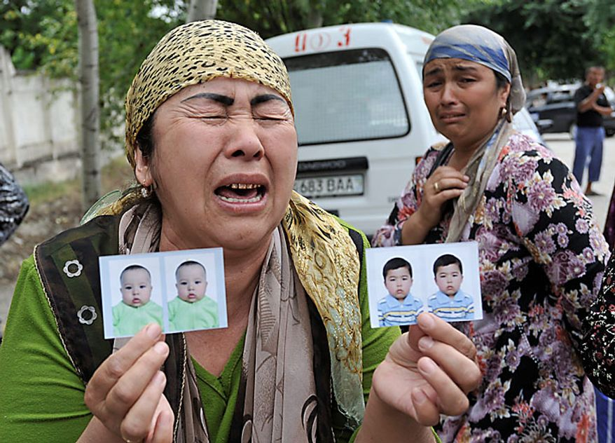 Ranokhon, a Uzbek woman who fled the southern Kyrgyz city of Osh, cries while showing photos of her grandchildren, from whom she became separated and whom she had to leave behind, as she waits for permission to cross into Uzbekistan at Jalal-Kuduk, Uzbekistan, on Tuesday, June 15, 2010. Uzbekistan closed the border Tuesday, leaving many camped out on the Kyrgyz side or stranded behind barbed-wire fences in a no man's land. (AP Photo/Anvar Ilyasov)