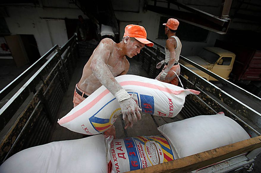 Kyrgyz Emergency Situation Ministry soldiers load flour bags on a truck at a grain elevator in Kara-Suu, a small town 14 miles northeast of Osh, Kyrgyzstan, as part of the first delivery of 70 tons of flour to the hungry in Osh on Tuesday, June 15, 2010. Rioting has killed at least several hundred people in this Central Asian nation, the Red Cross said Tuesday, as new reports strengthened suspicions that the violence was ignited deliberately to undermine the interim government. (AP Photo/Alexander Zemlianichenko)