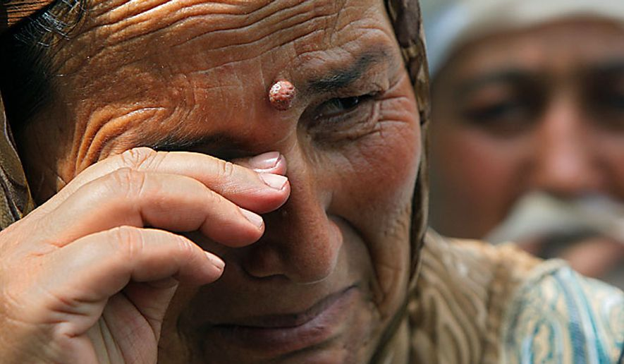 A Uzbek woman who fled the southern Kyrgyz city of Osh cries as she waits for permission to cross the Kyrgyz-Uzbek border into Uzbekistan on Tuesday, June 15, 2010. Uzbekistan closed the border Tuesday, leaving many camped out on the Kyrgyz side or stranded behind barbed-wire fences in no man's land. (AP Photo/Sergei Grits)