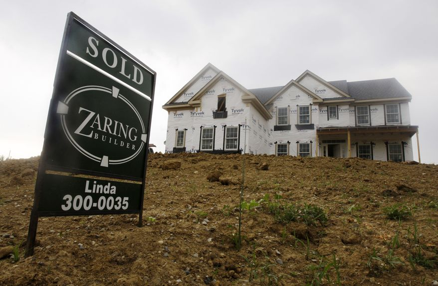 """A """"sold"""" sign is posted outside a new house under construction in Cincinnati on Wednesday, June 2, 2010. (AP Photo/Al Behrman)"""