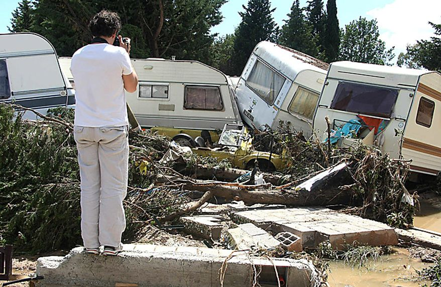 A woman photographs a camp site in Le Muy, France, on Wednesday, June 16, 2010, after floods. Regional authorities in southeastern France say more than a dozen people have been killed and many are still missing in the aftermath of flash floods that followed powerful rainstorms. Unusually heavy rains recently in the Var region have transformed streets into muddy rivers that swept up trees, cars and other objects. (AP Photo/Lionel Cironneau)