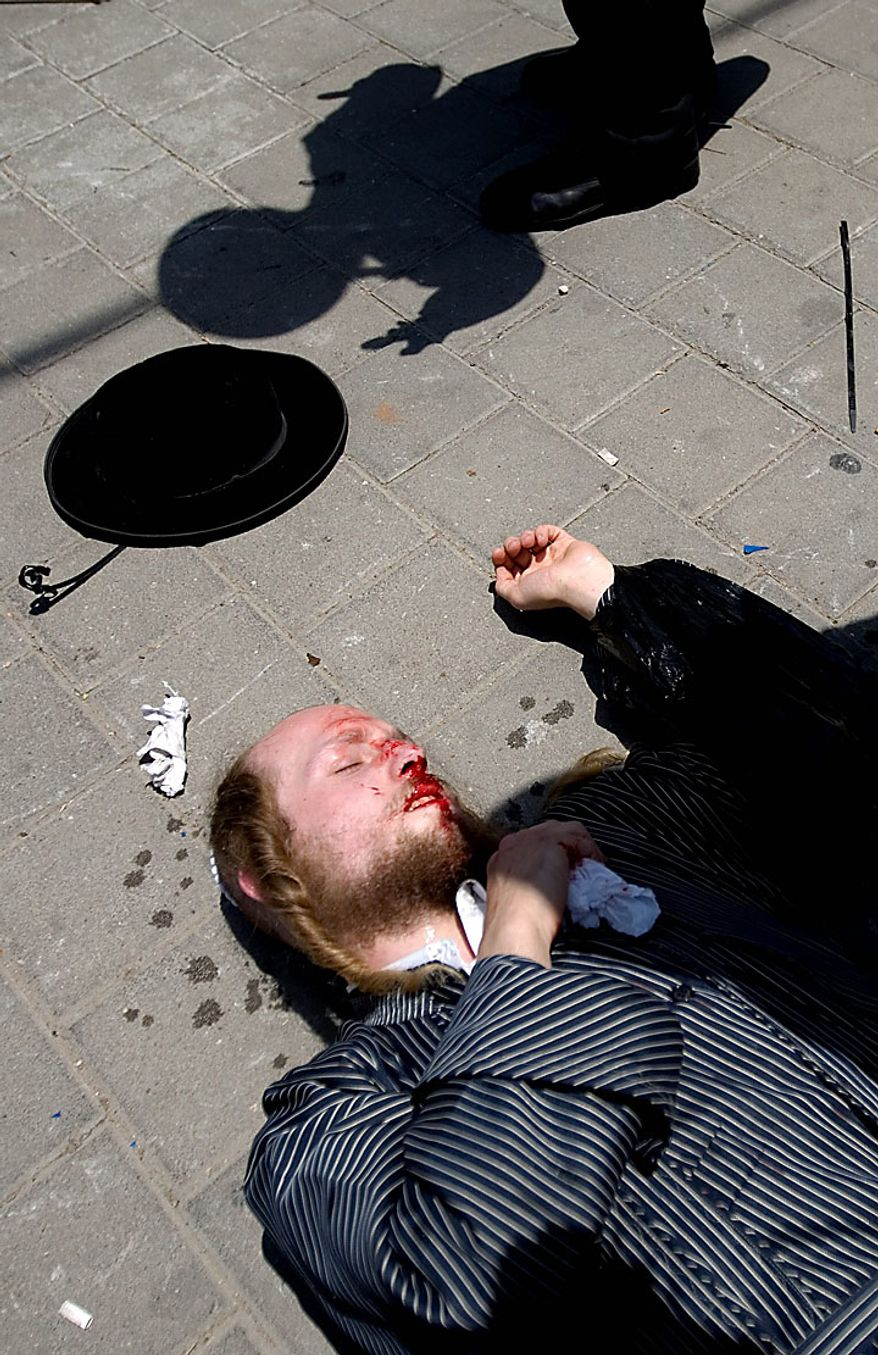 An ultra-Orthodox Jewish man lies on the ground with blood on his face after a scuffle with border police officers during a protest against the removal of ancient tombs in the neighborhood of Jaffa, Tel Aviv, Israel, Wednesday, June 16, 2010. Israeli police say they have arrested several dozen people in a violent protest by ultra-Orthodox activists opposed to an excavation they say is disturbing Jewish gravesites. Five police officers and 10 demonstrators were slightly wounded. (AP Photo/Ariel Schalit)