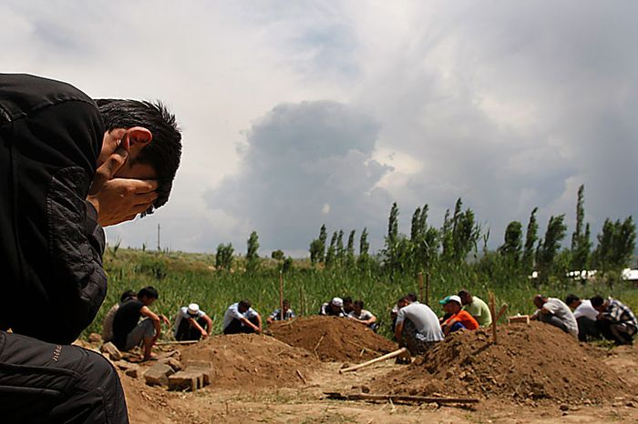 Uzbek men pray during a funeral for victims of ethnic rioting between Kyrgyz and ethnic Uzbeks in the southern Kyrgyz city of Osh on Wednesday, June 16, 2010. The official death count from the past week of violence rose to 189 on Wednesday, with 1,910 wounded, the Health Ministry said. Kyrgyzstan is observing three days of mourning for the victims of the recent mass-scale riots in the republic's southern regions. (AP Photo/Sergei Grits)