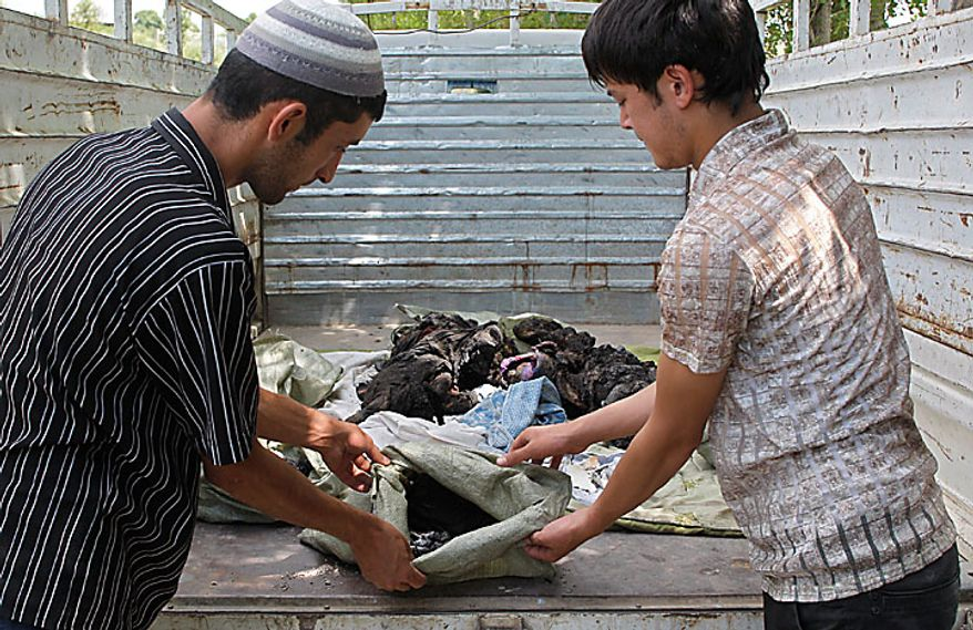 Uzbek men prepare to bury a victim of ethnic rioting between Kyrgyz and ethnic Uzbeks in the southern Kyrgyz city of Osh on Wednesday, June 16, 2010. Ethnic rioting has killed at least several hundred people, or roughly double official figures, the Red Cross said Tuesday, as new reports strengthened suspicions that the rioting in Kyrgyzstan was started deliberately. (AP Photo/Sergei Grits)