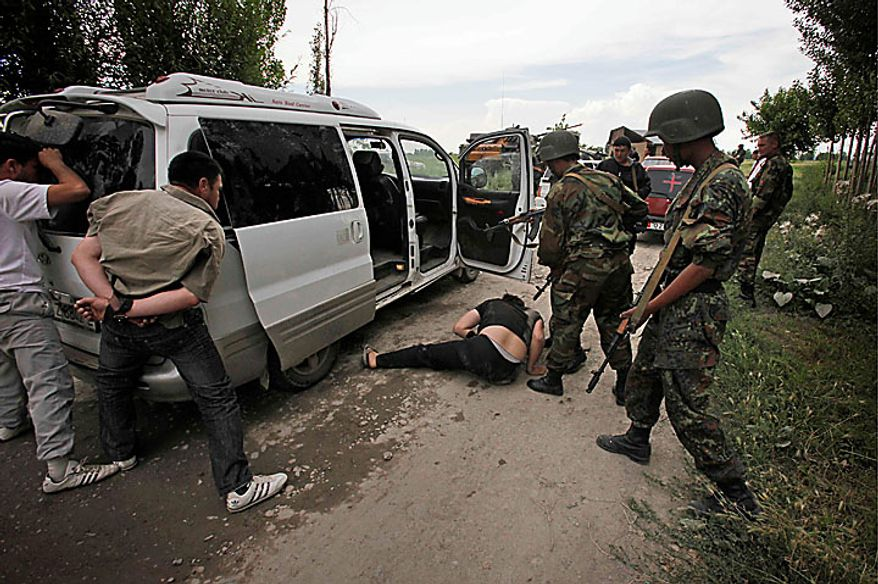 Kyrgyz soldiers and volunteers check passing cars and search passengers for weapons at a checkpoint on the Uzbek side the border near the southern Kyrgyz city of Osh on Wednesday, June 16, 2010. Heavy arms fire rang out over Osh before dawn Wednesday as authorities struggled to bring order to the country's south, which has been thrust into chaos by days of deadly ethnic riots. The violence has prompted more than 100,000 Uzbeks to flee for their lives to Uzbekistan, with tens of thousands more camped on the Kyrgyz side or stranded in a no man's land. (AP Photo/Alexander Zemlianichenko)