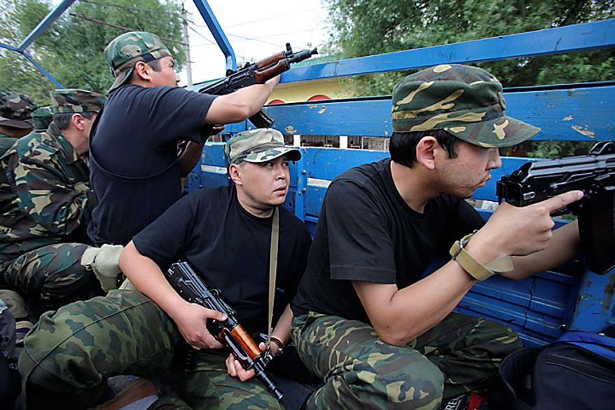 Kyrgyz army volunteers are on alert in the back of a truck patrolling the outskirts of Osh, Kyrgyzstan, on Wednesday, June 16, 2010. Heavy arms fire rang out over Osh before dawn Wednesday as authorities struggled to bring order to the country's south, which has been thrust into chaos by days of deadly ethnic riots. The violence has prompted more than 100,000 Uzbeks to flee for their lives to Uzbekistan, with tens of thousands more camped on the Kyrgyz side of the border or stranded in a no man's land. (AP Photo/Alexander Zemlianichenko)