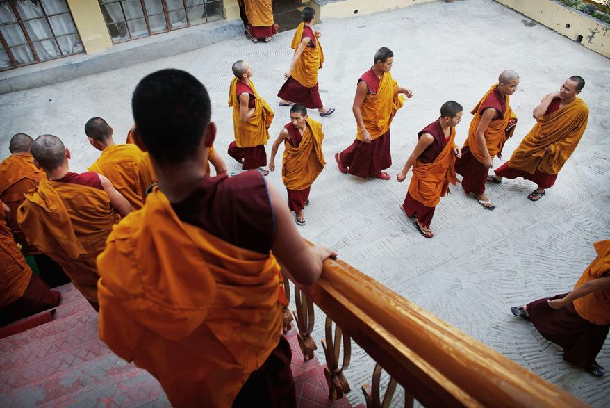 Associated Press photographs Buddhist monks leave a prayer session in northern India. The Dalai Lama, the center of the Tibetan exile movement, is approaching his 75th birthday, and many are wondering what will happen when he dies.