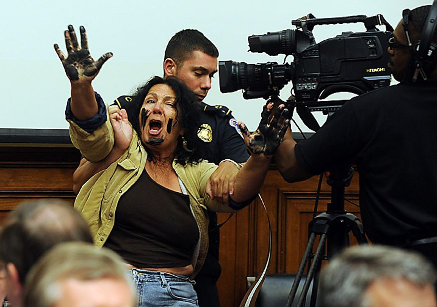 A protester is controlled by a Capitol Hill Police Officer while she calls for BP CEO Tony Hayward to be charged with a crime as he began to testify before the House Energy and Commerce Oversight and Investigations Subcommittee regarding BP's Deepwater Horizon oil rig explosion and oil spill on Capitol Hill in Washington on June 17, 2010.    UPI/Roger L. Wollenberg