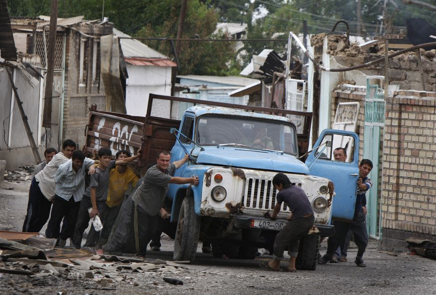 Ethnic Uzbek men push a truck as they build a barricade in the Uzbek district in the southern Kyrgyz city of Osh on Thursday, June 17, 2010. Some 400,000 people have been displaced by ethnic violence in southern Kyrgyzstan, the United Nations announced Thursday, dramatically increasing the official estimate of a refugee crisis that has left throngs of desperate, fearful people without enough food and water in grim camps along the Kyrgyz-Uzbek border. (AP Photo/Sergei Grits)