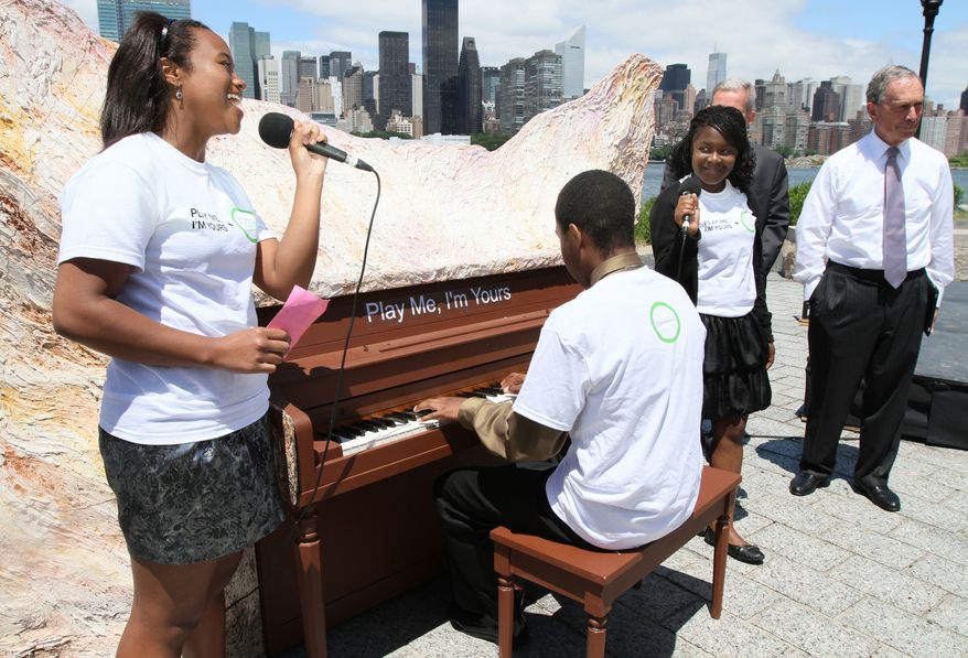 """Mayor Michael Bloomberg, right, stands by as Jaela Cheeks-Lomax, 16, left, Samantha Bogle, 16, foreground second from right, and Alexander Long, 18, at the piano, perform during a press conference announcing the public art project, """"Play Me, I'm Yours"""" on Thursday,  June 17, 2010 at Gantry Plaza State Park in the Queens borough of New York. The two-week project, which will feature 60 public pianos in locations throughout the five boroughs, is scheduled to kick off June 21. (AP Photo/Tina Fineberg)"""