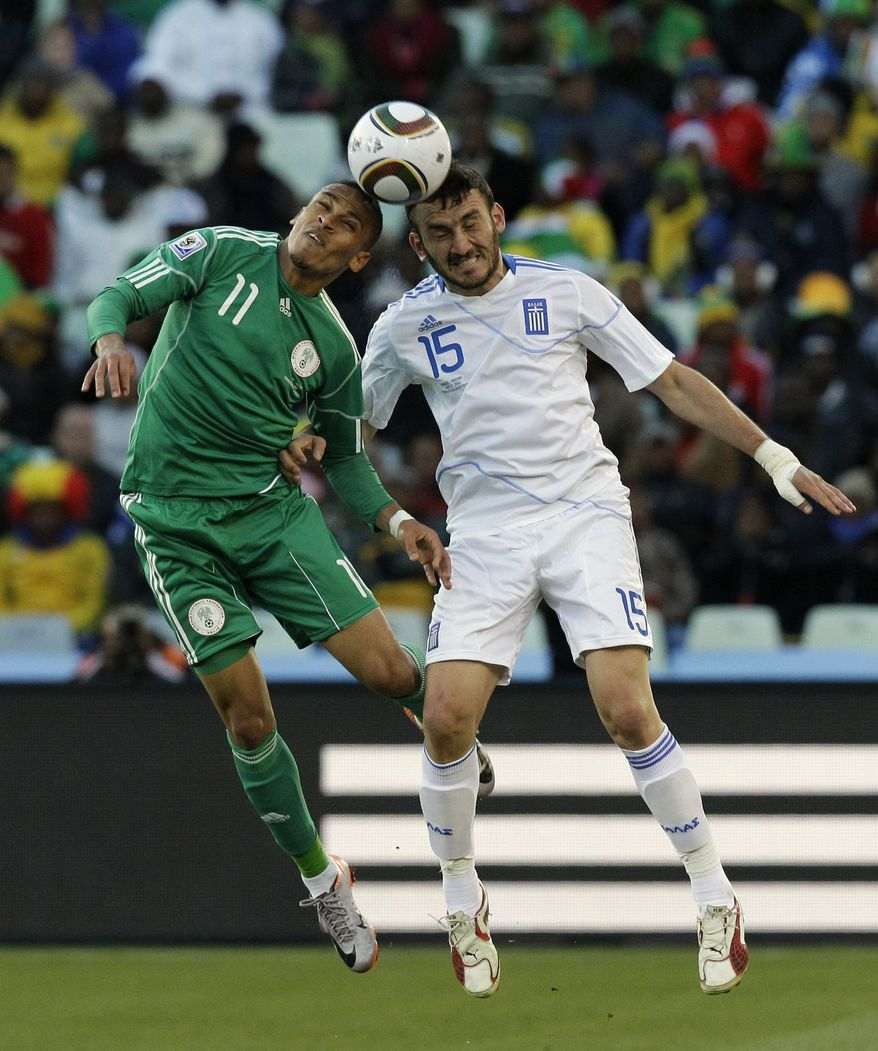 Greece's Vassilis Torosidis, right, and Nigeria's Peter Odemwingie, left, head the ball during the World Cup Group B soccer match between Greece and Nigeria at Free State Stadium in Bloemfontein, South Africa, Thursday, June 17, 2010. (AP Photo/Rick Bowmer)