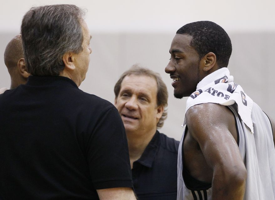 Kentucky's John Wall, right, talks with Washington Wizards basketball coach Flip Saunders, second from right, and Wizards team president Ernie Grunfeld, left, during a pre-NBA draft basketball workout for the Washington Wizards, Thursday, June 17, 2010, in Washington. Behind Grunfeld at left is Washington Wizards assistant coach Sam Cassell.