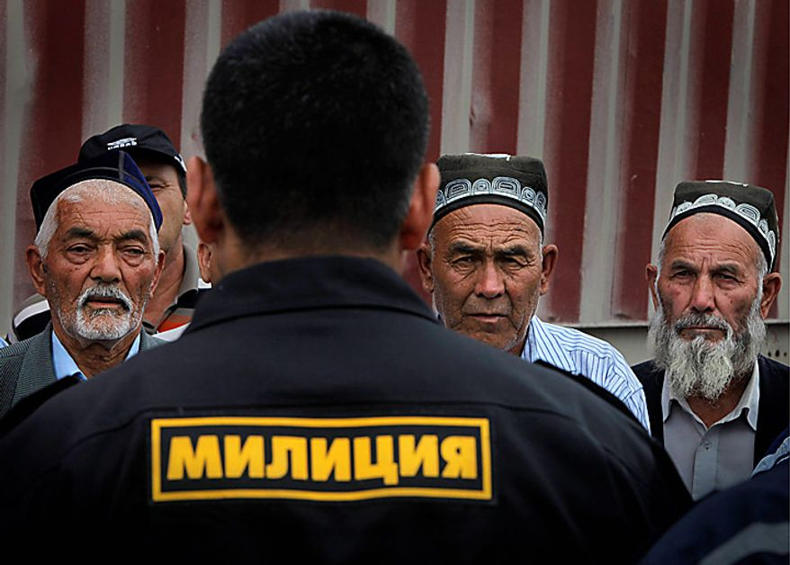 Ethnic Uzbek citizens listen to the head of local police, Col. Kursan Asanov, back to camera, during negotiations with local people in the Uzbek district of the southern Kyrgyz city of Osh, Kyrgyzstan onn Thursday, June 17, 2010. Hundreds of thousands of Uzbeks fled their homes seeking refuge in neighboring Uzbekistan after deadly rampages by mobs of ethnic Kyrgyz. (AP Photo/Alexander Zemlianichenko)