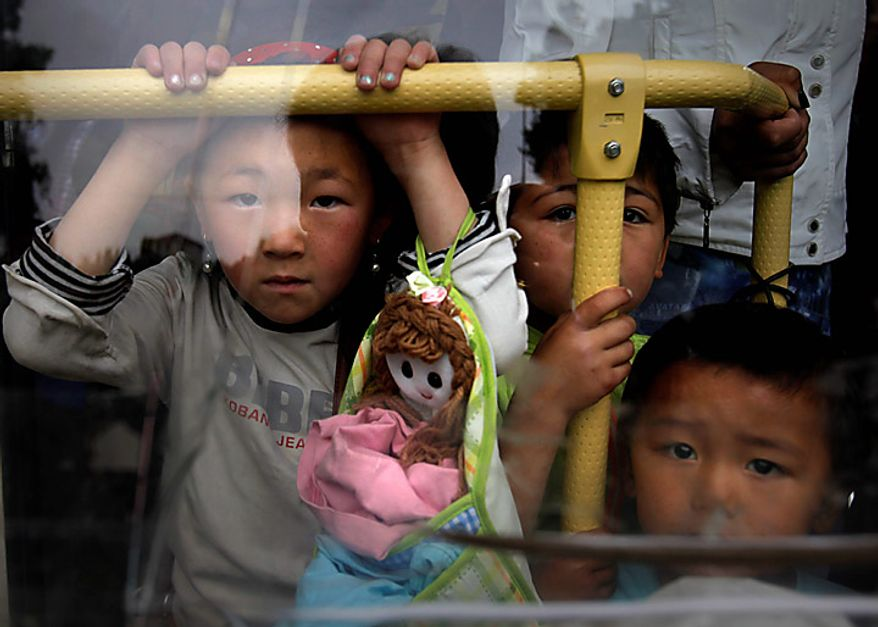Local children seen through a bus window as they leave the southern Kyrgyz city of Osh for the airport in Kyrgyzstan on Thursday, June 17, 2010. Hundreds of thousands of Uzbeks fled their homes seeking refuge in neighboring Uzbekistan after deadly rampages by mobs of ethnic Kyrgyz. (AP Photo/Alexander Zemlianichenko)
