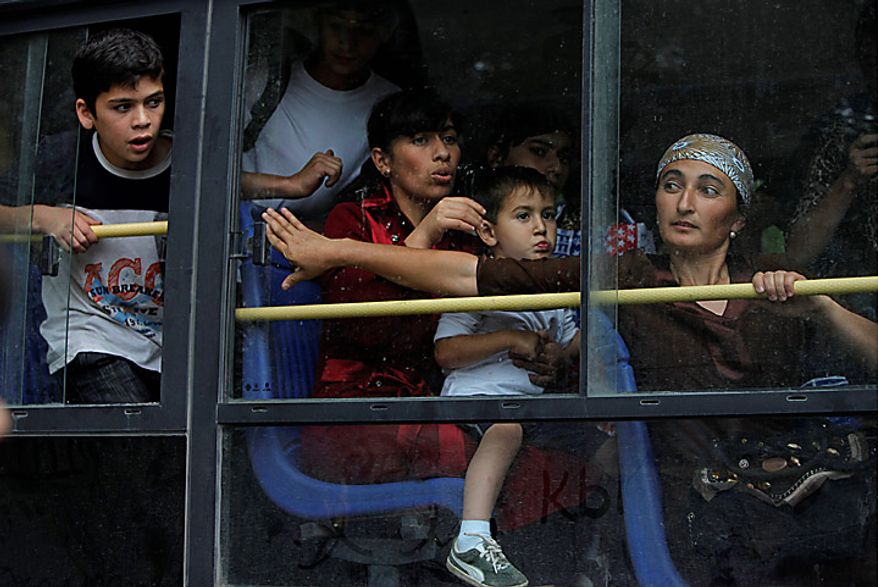 Local citizens seen through a bus window as they leave the southern Kyrgyz city of Osh for the airport in Kyrgyzstan on Thursday, June 17, 2010. Hundreds of thousands of Uzbeks fled their homes seeking refuge in neighboring Uzbekistan after deadly rampages by mobs of ethnic Kyrgyz. (AP Photo/Alexander Zemlianichenko)