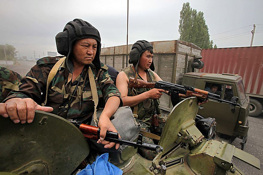 Kyrgyz soldiers are alert atop an armored personal carrier patrolling the outskirts of the southern Kyrgyz city of Osh in Kyrgyzstan on Thursday, June 17, 2010, with a humanitarian convoy behind the truck. Hundreds of thousands of Uzbeks fled their homes seeking refuge in neighboring Uzbekistan after deadly rampages by mobs of ethnic Kyrgyz. (AP Photo/Alexander Zemlianichenko)