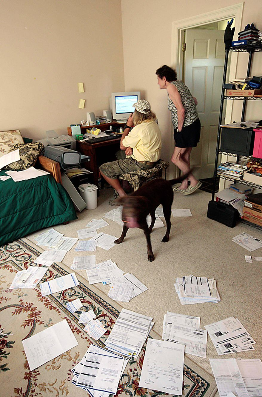 """Boat captain Brent """"Hollywood"""" Shaver and his wife are surrounded by bills as they study their computer at their Orange Beach, Ala., home Thursday, June 10, 2010.  Shaver, a long time charter boat operator, is shutting down his inshore fishing business because of the gulf oil spill. (AP Photo/Dave Martin)"""