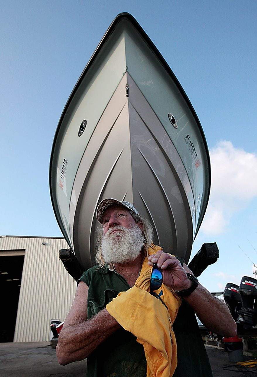 """Boat captain Brent """"Hollywood"""" Shaver cleans his sunglasses after pressure washing the oil off his boat Thursday, June 10, 2010.  Shaver, a long time charter boat operator, is shutting down his inshore fishing business because of the gulf oil spill. (AP Photo/Dave Martin)"""