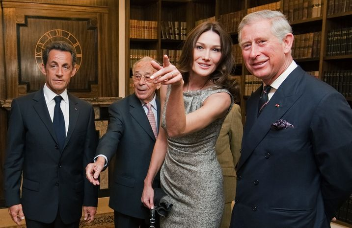 French President Nicolas Sarkozy, left, his wife Carla Bruni-Sarkozy, second right, and Britain's Prince Charles, right, look at photographs of French President Charles De Gaulle during a visit to London headquarters of the Free French, the fighters led by de Gaulle, who rejected their country's surrender to Nazi Germany, on Friday June 18, 2010. Mr. Sarkozy marked the 70th anniversary of de Gaulle's defiant World War II broadcast from London on Friday, visiting the studio where the leader urged his compatriots to resist the German occupation. (AP Photo/Leon Neal, Pool)