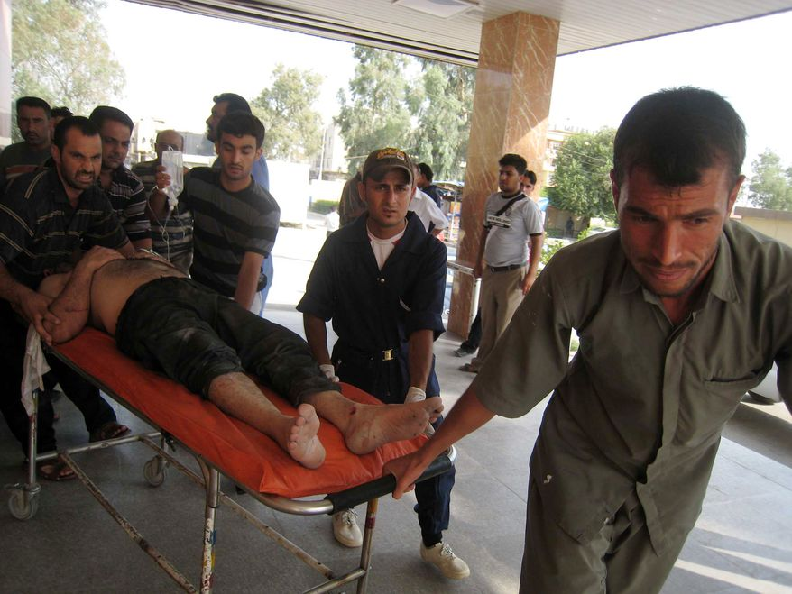 An injured man is rushed to a hospital after a car bombing in Tuz Khormato, in northern Iraq, Friday, June 18, 2010. Car bombs, meanwhile, tore through two neighborhoods in restive cities north of Baghdad in separate attacks targeting a police captain and a provincial council member. The deadliest attack was in the northern city of Tuz Khormato when an explosives-laden car blew up about 50 yards (meters) from the house of Niazi Mohammed, a Turkomen member of the Salahuddin provincial council, according to police. (AP Photo/Emad Matti)
