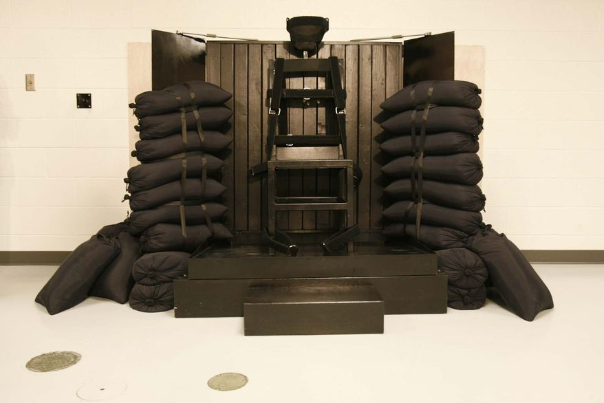 The execution chamber at the Utah State Prison after Ronnie Lee Gardner was executed by firing squad Friday, June 18, 2010. Four bullet holes are visible in the wood panel behind the chair. Gardner was convicted of aggravated murder, a capital felony, in 1985. (AP Photo/Trent Nelson - Pool)