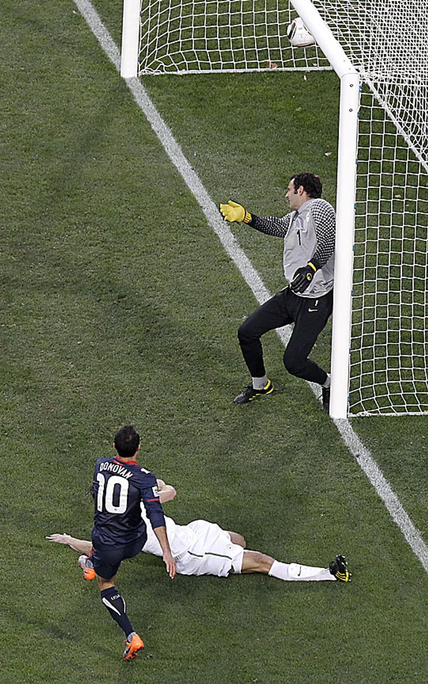 United States' Landon Donovan, foreground, scores a goal against Slovenia goalkeeper Samir Handanovic, right, during the World Cup group C soccer match between Slovenia and the United States at Ellis Park Stadium in Johannesburg, South Africa, Friday, June 18, 2010.  (AP Photo/Tom Curley )