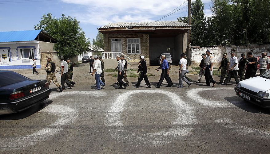 Kyrgyz and ethnic Uzbek men walk along an SOS sign on the street of Suzak, the Uzbek neighborhood near the southern Kyrgyz city of Jalal-Abad, Kyrgyzstan, Friday, June 18, 2010, as they perform joint Kyrgyz-Uzbek patrol. Some 400,000 people have been displaced by ethnic violence in southern Kyrgyzstan, the United Nations announced Thursday, dramatically increasing the official estimate of a crisis that has left throngs of desperate, fearful refugees without enough food and water in grim camps along the Uzbek border. (AP Photo/Sergey Ponomarev)