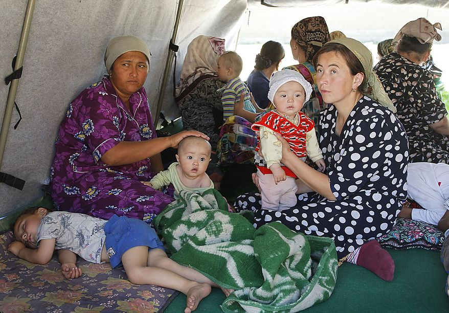 Ethnic Uzbek women and children sit in a tent near Uzbek-Kyrgyz border in outskirts southern city of Osh, Friday, June 18, 2010. The United Nations said as many as 1 million people may need aid in Kyrgyzstan and Uzbekistan, including the potential number of refugees, internally displaced, host families and others that may suffer in one way or another from the unrest. (AP Photo/Sergei Grits)