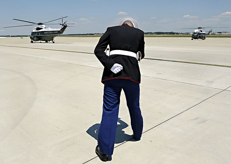 A U.S. Marine leans into the rotor wash as President Obama, aboard Marine One, left, prepares to take off from Andrews Air Force Base, Md., Friday, June 18, 2010. (AP Photo/Cliff Owen)