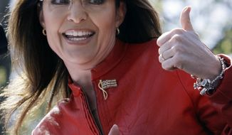 In this April 14, 2010 file photo, Sarah Palin flashes a thumbs-up towards her husband, Todd, as she begins to address a crowd during a stop of the Tea Party Express on Boston Common in Boston. After months of requests from reporters, a California university on Friday, June 18, 2010 agreed to allow members of the media to attend a fundraiser next week featuring Sarah Palin. (AP Photo/Charles Krupa, File)