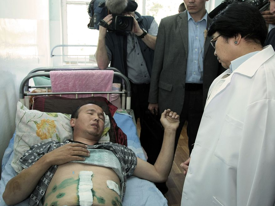 Kyrgyzstan's interim government leader Roza Otunbayeva, right, speaks to a wounded ethnic Kyrgyz citizen in the southern Kyrgyz city of Osh, Kyrgyzstan, Friday, June 18, 2010. She is vowing to work for the return of refugees who fled deadly ethnic violence there by the hundreds of thousands. (AP Photo/Kyrgyz Presidential Press Service, Sagyn Alchiyev, pool)