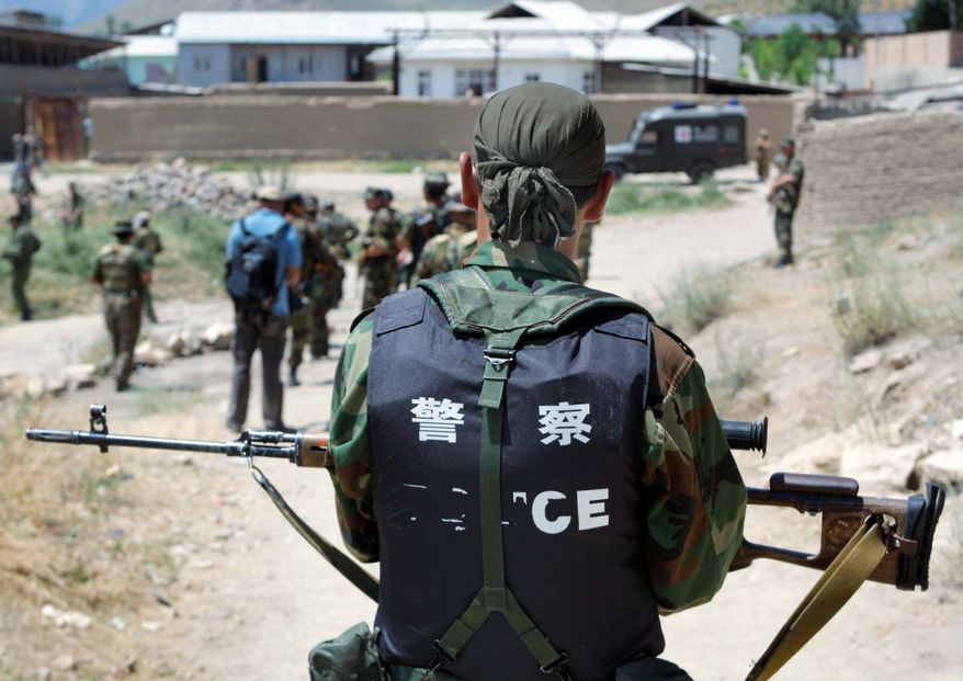 Kyrgyz soldiers conduct a foot patrol in Suratash, Kyrgyzstan. Soldiers tried to reassure refugees it was safe to return home, but many refused to go. (Associated Press)