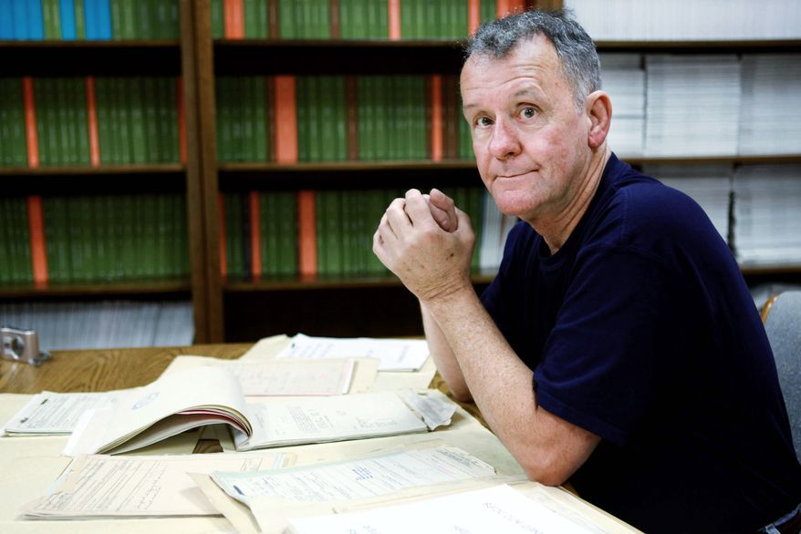 Ted Darcy, of Fall River, Mass., is surrounded by documents on his research into the identity of soldiers missing in action from WWII, while at the National Records Center in Suitland, Md. (Associated Press)
