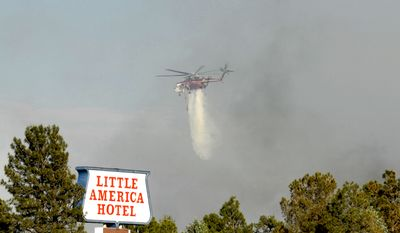 A Forest Service helicopter drops water on a wildfire behind the Little America Hotel in Flagstaff, Ariz., on Saturday, June 19, 2010. (AP Photo/Arizona Daily Sun, Rick Wacha)