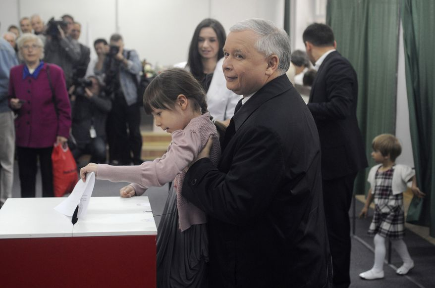 Presidential candidate Jaroslaw Kaczynski, twin brother of the late President Lech Kaczynski, who was killed in a plane crash in Russia, lifts his brother's granddaughter Eva to cast his vote in the presidential election in Warsaw on Sunday, June 20, 2010. Poles are voting Sunday to choose Lech Kaczynski's successor. (AP Photo/Alik Keplicz)
