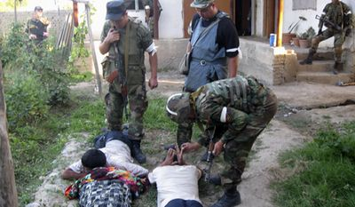 In this image made available by the Press Service of the Kyrgyz Interior Ministry, ministry forces conduct house-to-house searches in an Uzbek area in the village of Nariman on the edge of the main southern city of Osh, Kyrgyzstan, on Monday, June 21, 2010. (AP Photo/Press Service of the Kyrgyz Interior Ministry, Pool)