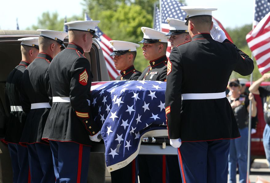 The casket is carried into the funeral for Marine Cpl. Jacob Leicht, the 1,000th American serviceman killed in Afghanistan, at the Impact Christian Fellowship church Saturday, June 5, 2010, in Kerrville, Texas. Cpl. Leicht, who was born on the Fourth of July, died several days before Americans honor fallen troops on Memorial Day. . (AP Photo/San Antonio Express-News, Tom Reel)