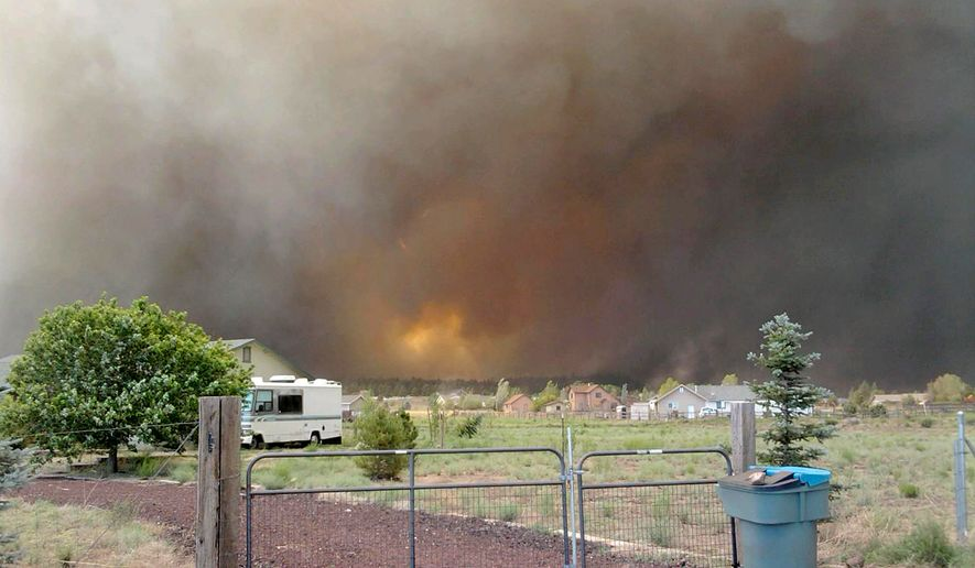 A new wildfire burns at Shultz Pass between the San Francisco Peaks and Mount Elden on Sunday, June 20, 2010, in Flagstaff, Ariz. Several neighborhoods were evacuated because of the blaze. (AP Photo/Michele Legg)