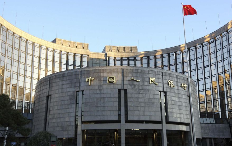 """In this Nov. 27, 2008, file photo released by China's Xinhua news agency, a Chinese flag flutters in front of the headquarters of the People's Bank of China in Beijing. China's central bank said Sunday June 20, 2010, it would maintain a stable exchange rate and didn't anticipate major changes in the value of the yuan, a day after saying it would manage the currency more flexibly. In a commentary on Saturday's announcement, the People's Bank of China attempted to assuage fears of a major strengthening of the yuan, also known as the renminbi, or """"people's money."""" (AP Photo/Xinhua, Gao Xueyu, File)"""