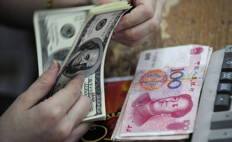 **FILE** A Chinese clerk counts U.S. dollars in exchange for the Chinese renminbi at a bank in Hefei in central China's Anhui province on June 20, 2010. (Associated Press)